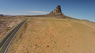 Aerial view of Agathla peak with Monument Valley road (163) in the foreground