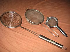 Several wire meshes shaped like bowls, with metal handles.
