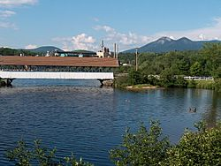 Covered bridge over the Upper Ammonoosuc River in front of former paper mill in Groveton.  The Percy Peaks are in the distance.