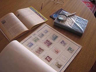 Chilean stamp album and catalogue, and a magnifying glass