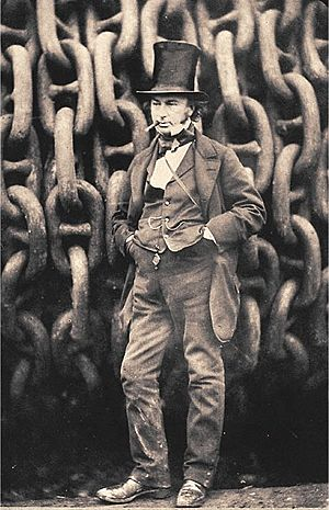 A 19th century man wearing a jacket, trousers and waistcoat, with his hands in his pockets and a cigar in mouth, wearing a tall stovepipe top hat, standing in front of giant iron chains on a drum.