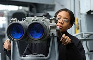 US Navy 021206-N-1328C-501 Signalman 3rd Class Tiffany Culereth from Bronx, N.Y., observes ships in the area through binoculars called ^ldquo,Big Eyes.^rdquo,