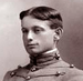 Head of a young man with neatly combed and parted hair wearing a military cadet's jacket, with cords running horizontally across the chest and a high, stiff collar.