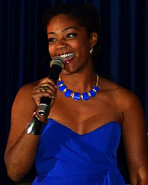 A Black woman in a blue dress in front of dark blue curtains