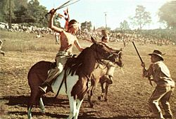 A young boy on horseback, recreating the Indian Raid during the Flax Scutching Festival