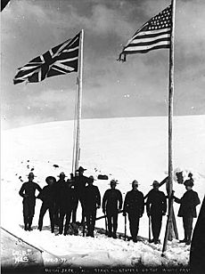 North-West Mounted Police standing next to American and British flags marking the boundary between Alaska and British Columbia (HEGG 446)