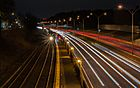 artsy long-exposure of car lights on a highway, with a train