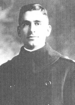 Head and shoulders of a young white man with a cleft chin and neatly combed hair parted at the side. He is wearing a dark, heavy, pea coat with military shoulder straps.