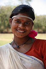 A dark-skinned woman with a bindi, tilting her head and smiling at the camera