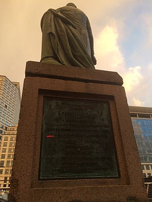 Sign of statue of robert milligan in canary wharf edited