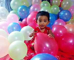 One year baby is playing with birthday balloons