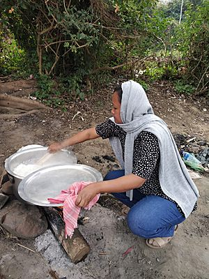 A woman in jeans and cooking in traditional way