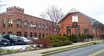 Two brick buildings viewed from their right, across a road. The one on the left has a castle-like tower on the corner; the one on the right has a decorative white wooden pointed roof. There is a parking lot in front of them on the left with some cars.