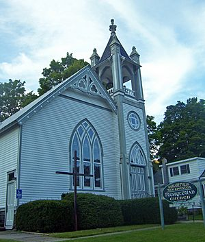 "A white church with arched windows and an ornate belfry. In front are a wooden cross and a sign saying ""Margaretville New Kingston Presbyterian Church"""