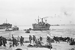 Troops come ashore on one of the Normandy invasion beaches, past the White Ensign of a naval beach party, 7 June 1944. A24012