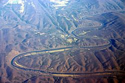 Oblique air photo of the meandering Potomac River at Little Orleans (center), facing north. The photo shows Allegany County, Maryland (left), Morgan County, West Virginia (right), Sideling Hill (right), and the Chesapeake and Ohio Canal.