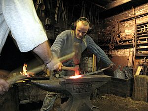 3 tourist helping artist blacksmith in finland