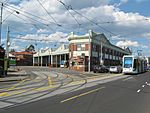 A photo of Kew tram depot. There is one C-class stabled and another C-class is passing the depot on Barkers Road.