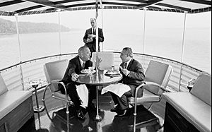 President Johnson has dinner with guest aboard the Sequoia as Secret Service Agent Rufus Youngblood stands in the background, July 15, 1965