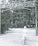 "Woman in a long dress in front of a sign across a road. Wooden letters read ""Camp Curry""."