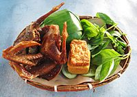 Fried pigeon with nasi timbel (banana leaf wrapped rice), tempeh, tofu and vegetables, Sundanese cuisine, Indonesia