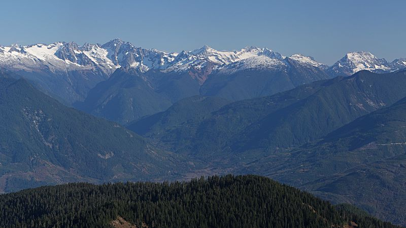 A range of snow-capped mountains. In the foreground is a stretch of forest. In between is an area of lower ground.