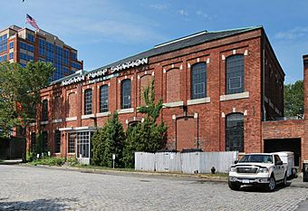 "A wide two-story brick building with a hipped roof and gently arched windows, some of which have been bricked in. Across the top is a sign saying ""Albany Pump Station."" There is a taller building on the left."