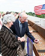 US Navy 090824-N-9876C-013 Retired Navy captain and former astronaut Jim Lovell and his wife, Marilyn Gerlach, sign the final roofing beam to be lifted into place during the topping off ceremony for the Captain James A. Lovell