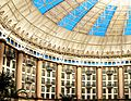Interior of a domed atrium surrounded by hotel rooms and tall columns with light coming in through blue windows