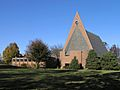 Red brick church with triangular facade and tall, sloping roof