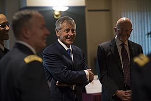 Secretary of Defense Chuck Hagel, center, shares a laugh with other guests before a retirement ceremony for U.S. Army Gen. Keith B. Alexander March 28, 2014, at the National Security Agency (NSA) at Fort George 140328-D-EV637-372