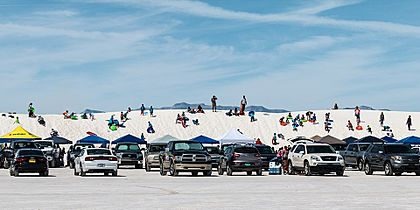 Visitors sledding and picnicking at White Sands National Park, New Mexico, United States