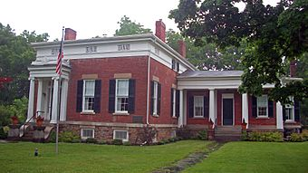A brick house with a much larger, more decorated, flat-roofed section on the left with four chimneys on top and a smaller, plainer gabled wing on the right with one chimney