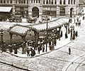 Historic photograph of the Pioneer Square Pergola with the Pioneer Building behind. Many people wait under the Pergola as the cobbled streets bustle around them.