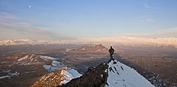 An ISAF member stands on top of a hill watching a snow-covered mountain range in Kabul province