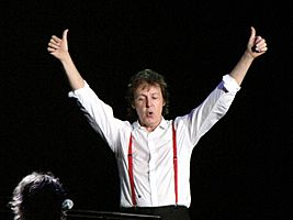 A man in his early sixties, wearing a white shirt and red suspenders during a concert on FedEx Field in Landover, Maryland, 1 August 2009, standing in a pose of victory.
