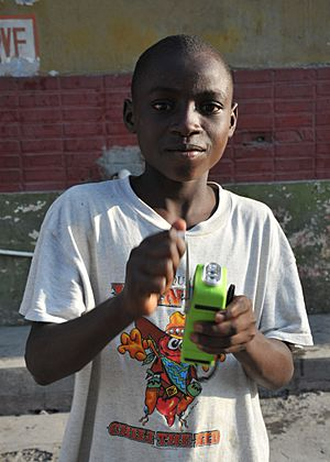 US Navy 100124-N-6214F-019 A Haitian child uses the hand crank on his multi-purpose self-powered radio