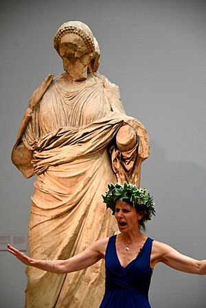 An actress performing a play. She wears a laurel wreath and stands in front of a statue of a woman from the Mausoleum at Halicarnassus. Room 21, The British Museum, London