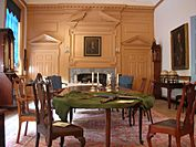 A room with large table and fireplace