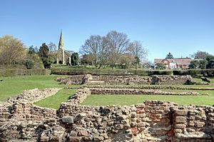 Low reddish-coloured stone walls, the construction of which suggests antiquity, lie in a grassy area backed by the outline of a modern settlement including a church with a spire. The trees lack leaves and the sky is a clear blue.