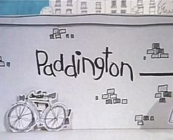 "In this animation title card, the name ""Paddington"" is scrawled on a drawing of a brick wall. A bicycle leans against the wall, and a sliver of blue sky and tall buildings are visible over the wall's top edge."