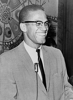 Un hombre de 38 años con traje y corbata sonríe ampliamente.años con traje y corbata sonríe ampliamente. Lleva gafas y un micrófono al cuello.