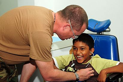 US Navy 081028-N-3173B-027 Cmdr. John King assesses the reflexes of a Cerebral Palsy patient at the Arima District Health Facility as part of the humanitarian-civic assistance mission Continuing Promise (CP) 2008.jpg