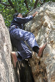 Visually impaired girl negotiating a rock while rock climbing