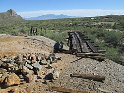 Mine dump and ruins of rail haulage at San Xavier. Helmet Peak is at the left and the Santa Rita Mountains are in the background.