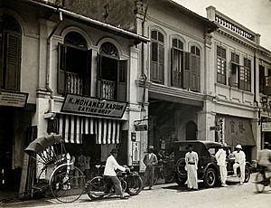 An arcade of shops with a road sweeper at work in the street of Kuala Lumpur, 1915-1925