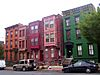 A group of five three-story brick rowhouses, two and three bays wide, on an urban street. The one on the right is painted green, the three in the middle have projecting bays on the upper stories and the leftmost one is unpainted.