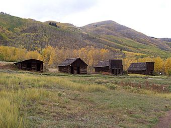 Four small old wooden houses seen at some distance with high hills in the background.