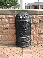 A black cast-iron hald-round post with a domed top. Around one metre high. It has the year '1877' in white raised lettering. It also says 'CITY OF NOTTINGHAM' in capital letters which is accompanied with the coat of arms of the City of Nottingham, and the word 'BOUNDARY' in capital letters below that.