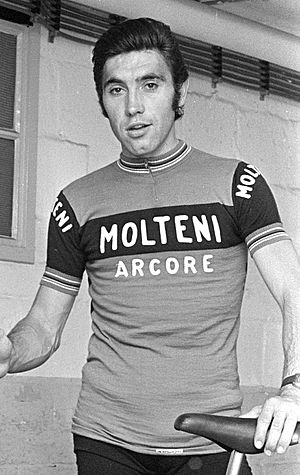 "A man holding a bicycle. The man's shirt says ""Molteni Arcore""."